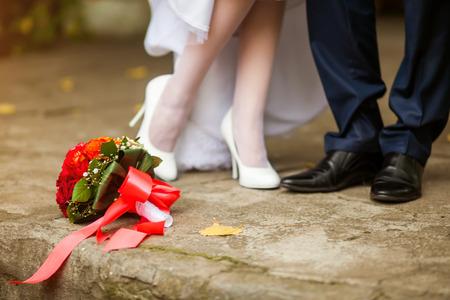 Feet in footwear of the groom and the bride