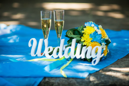 Word of wedding and bridal bouquet and glasses with champagne