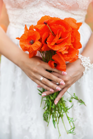 beautiful tender bridal bouquet of poppies holding bride