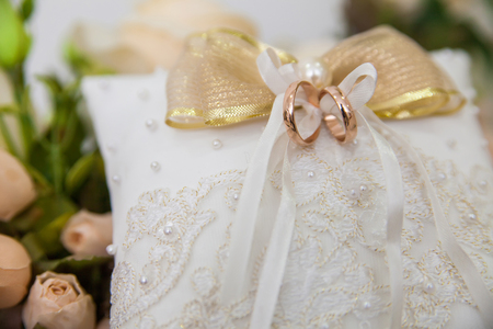 wedding rings on white lace pillow