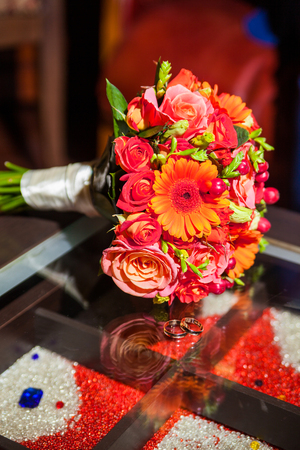 rings and beautiful tender bridal bouquet from different roses and other flowers close up