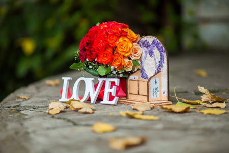 Word Love made with white  letters over the wooden surface next to the bouquet of flowers as a wedding Day composition, background