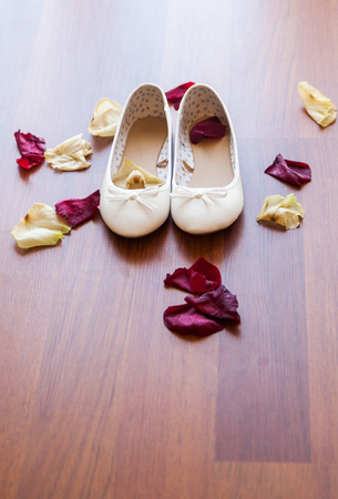Bridal shoes lie on the floor, scattered rose petals, in the light of the sun Stock Photo