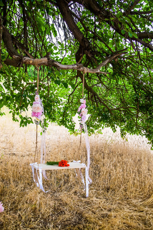 wedding bouquet of poppies on a wooden swing, swing hanging on a tree branch, entwined with flowers