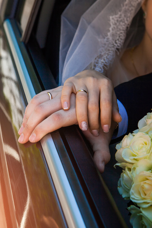 hands of the bride and groom and wedding bouquet on black box car