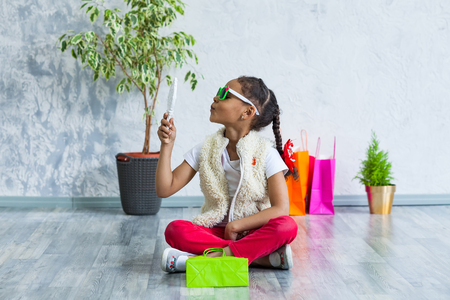 cute African girl Looking at newly purchased glasses