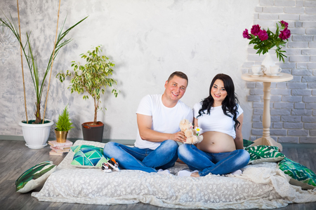 The concept of family, care and parenthood. A pregnant woman and her husband sitting on the bed at home and plying with a childrens shoes. Stock Photo