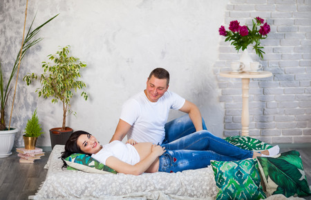 The concept of family and parenthood. A pregnant woman and her husband lying at home on the bed, Stroking a womans belly, smiling