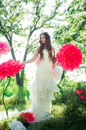 Beautiful happy bride in a white dress in the garden, among the huge flowers.