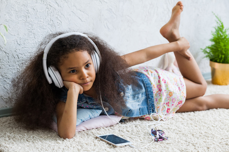 afroamerican: Bored African girl at home, listening to music in big white headphones