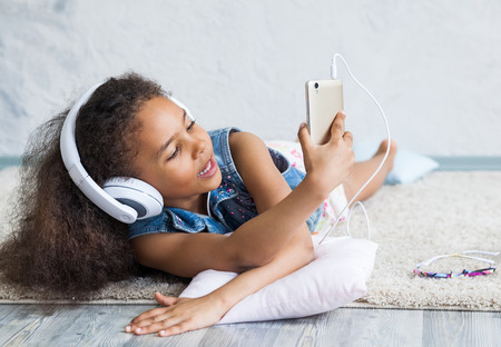 untruth: cute African girl at home, listening to music in big white headphones