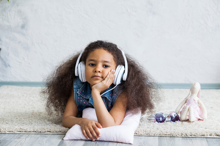 untruth: Bored African girl at home, listening to music in big white headphones