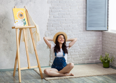 Getting creative. Woman artist painting a sunflower at home Фото со стока