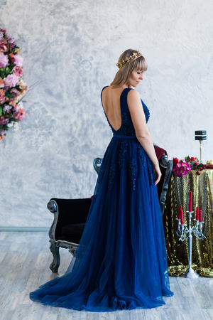 Beautiful blond Woman in blue dress posing in the ball room