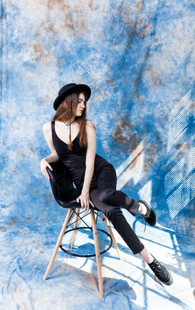 Studio shot of a magnificent young woman in elegant black clothes and classic hat. Beauty, fashion concept.