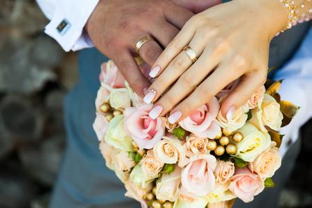 Primo piano delle mani dello sposo e della sposa, sullo sfondo di un bouquet colorato.