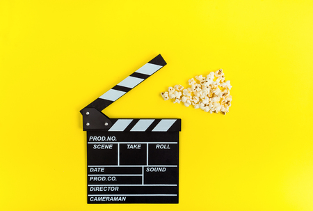 Cinema background. Film watching. Popcorn and clapperboard on yellow background top view copy space Stok Fotoğraf