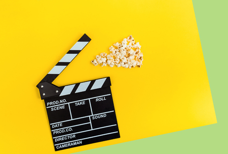 Cinema background. Film watching. Popcorn and clapperboard on yellow and Green background top view copy space Stok Fotoğraf