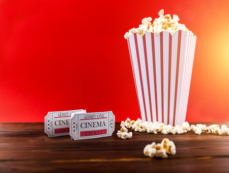 Red and White Bucket Of Popcorn With Two Red Movie Tickets. Movie Night Close Up On Red Stock Photo