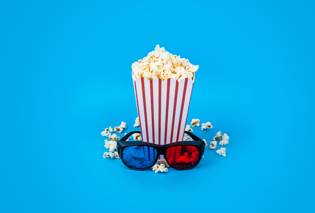 Cinema background. Film watching. Loose popcorn in striped box and 3d glasses on blue background