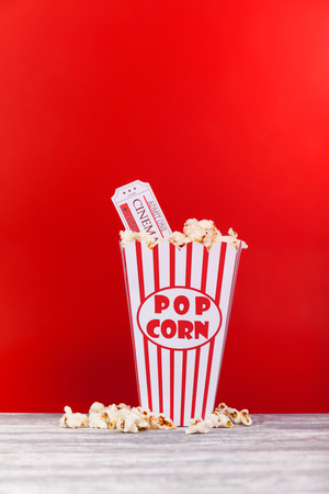 Vintage red striped old Popcorn box overflowing with two Tickets Stock Photo