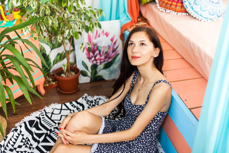Beautiful young teenage girl sitting on a sofa in a hotel room with a colorful interior enjoying a vacation. Summer vacation begins. Reklamní fotografie