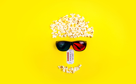 Abstract image of viewer, 3D glasses and popcorn, text movie on yellow background. Still life, top view, flat lay. Concept cinema and entertainment Stock Photo