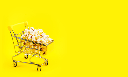 Popcorn in a shopping trolley on pink background top view Stock Photo