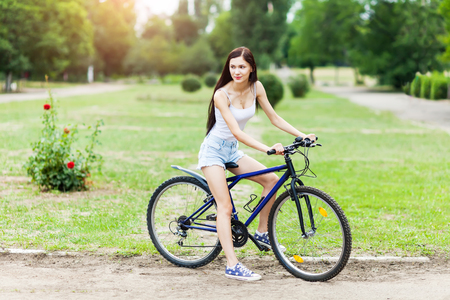 Beautiful girl riding a bicycle in a city park. Active people. Outdoors Stock Photo