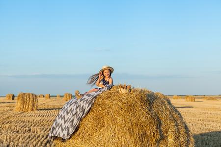 Adorable fille portant un chapeau de paille dans le village sur une botte de foin, buvez du lait et mangez des produits de boulangerie dans un champ de blé le soir d'été chaud et ensoleillé. Mignon petit enfant dans le champ de seigle au coucher du soleil. Banque d'images
