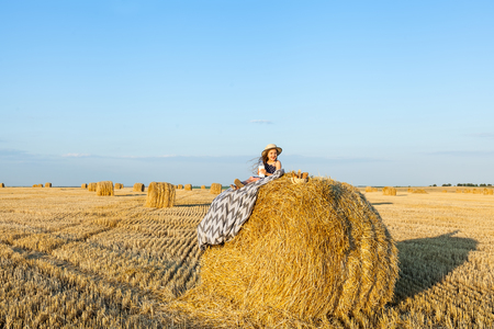 Adorable girl wearing straw hat in the village on a haystack, drink milk and eat baked goods in wheat field on warm and sunny summer evening. Cute little child in rye field on sunset.