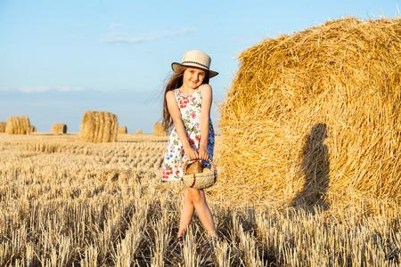 Aanbiddelijk meisje dat strohoed draagt die gelukkig in tarweveld loopt op warme en zonnige zomeravond. Schattig klein kind in rogge veld op zonsondergang met een mandje brood.