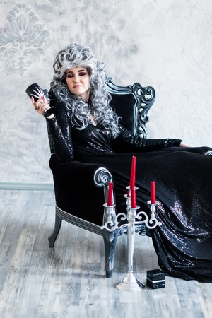 Halloween. Portrait of a gorgeous young glamour beautiful woman vampire baroque aristocrat witch in black dress with gray curly hair with a black glass in the ancient castle.