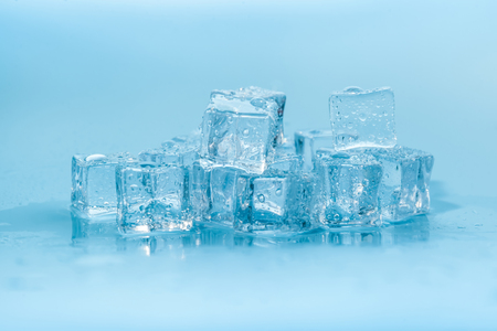 Wet ice cubes on blue background Stock Photo