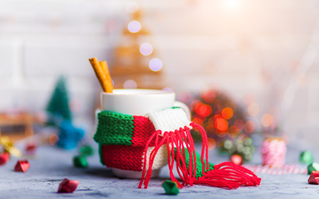 Mug Of Hot Coffee Or Tea with mini marshmallows and cinnamon with green red white scarf against a rustic background with beautiful Christmas lights of bokeh with toys