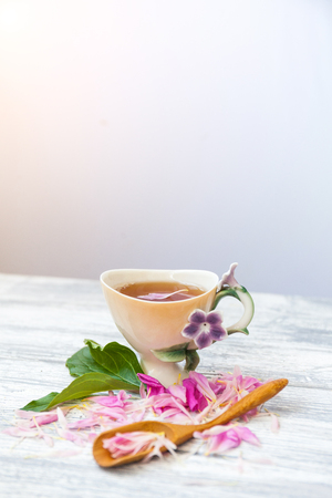 Cup of green tea and spring peonies blossom on a old wooden background. Rustic.