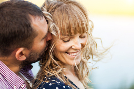 Close-up portrait of couple with wind in hair, hugging and happy together soft focus Banco de Imagens