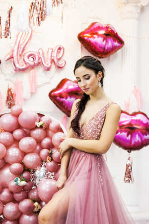 Portrait of Young Woman in Beautiful Tulle Dress in the interior decorated with balloons Pink heart, Love and lips. Women's Day. March 8 Stock fotó