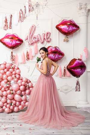 Girl in Tulle Dress with Flower. Baloon Pink heart Background. Celebrating Women's Day. March 8. Smiling Happy Surprised Woman with Baloons. Happy Emotions. Loves Pink Kisses Baloon. Stock fotó