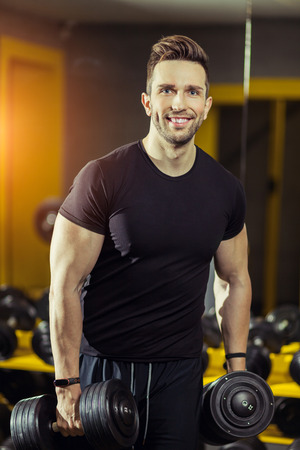 Concept Power Strength Healthy Lifestyle Sport Powerful Muscular man working out in gym doing exercises at biceps with dumbbells Stockfoto