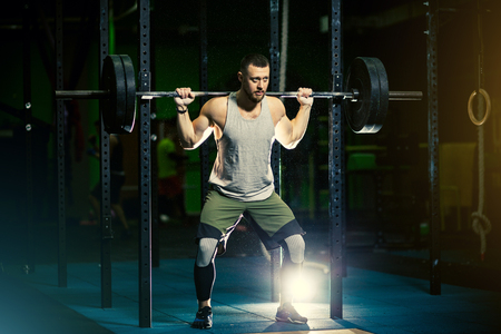 Strong motivated muscular bodybuilder man holding a heavyweight barbell on the shoulder behind the neck while crouching and doing squats exercise in the dark gym.