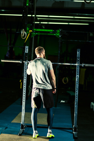 Strong motivated muscular bodybuilder man in the dark gym thinking about sprot and planning workout, stands with his back, looks into the distance, have a rest Stock Photo