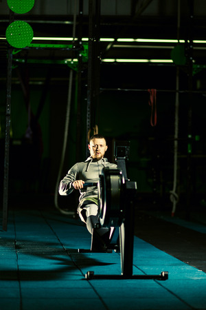 Handsome strong Athlete is doing workout on the rowing machines at the gym