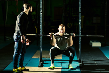 Fitness trainer and Strong motivated muscular bodybuilder man holding a heavyweight barbell on the shoulder behind the neck while crouching and doing squats exercise in the dark gym.