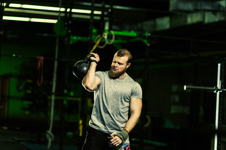 Strong motivated muscular bodybuilder man holding a weight on the shoulder while crouching and doing squats exercise in the dark gym. Stock Photo