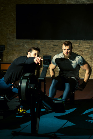 Athlete and his fitness trainer is doing workout on the rowing machines at the gym