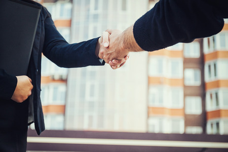 Businessmen shaking hands on background of new builing Imagens - 122322712
