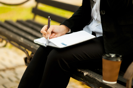 Happy businesswoman calling on mobile phone and taking notes to notepad on the street, outdoor Stok Fotoğraf