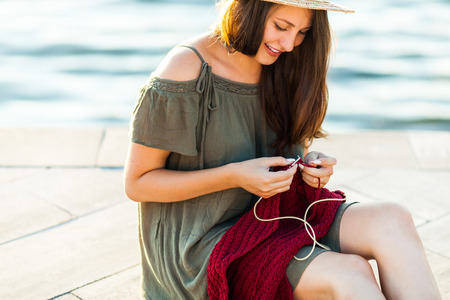 A young woman sitting on the river bank and knitting a sweater with knitting needles on a summer day. Get Creative everywhere