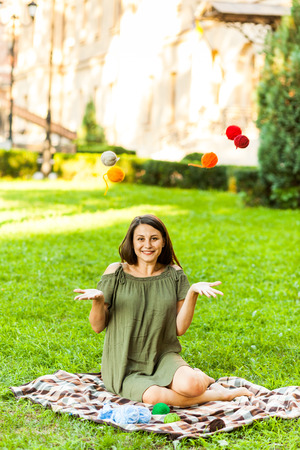 A young woman sitting in a city park on green grass and knitting a sweater with knitting needles on a summer day. Get Creative everywhere 版權商用圖片